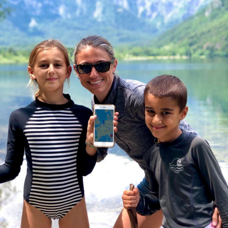 A mom with her two children in front a mountain and lake. She is holding a phone with a screenshot of the Gowhee app.